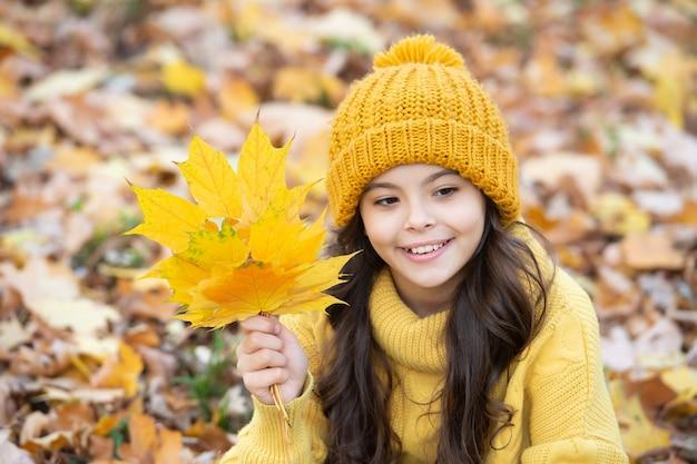 Jesienna moda. portret teen dziewczyna w kapeluszu trzymać jesienny liść. szczęśliwe dziecko zabawy z żółtym liściem klonu na naturalnym tle. jesień natura. wrzesień. naturalne piękno.