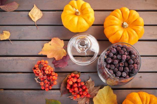 Jesienna nastrojowa kompozycja na szarym drewnianym stole z dyniami, jarzębiną i liśćmi. szklany otwarty słoik z suszonym głogiem