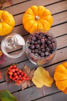 Jesienna nastrojowa kompozycja na szarym drewnianym stole z dyniami, jarzębiną i liśćmi. szklany słoik z suszonym głogiem na herbatę.
