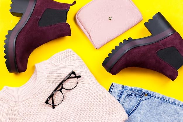 Jesienna odzież damska - różowy sweter, niebieskie dżinsy, skórzana torebka, masywne botki, akcesoria