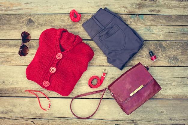 Jesienna odzież i akcesoria damskie: czerwony sweter, spodnie, torebka, koraliki, okulary przeciwsłoneczne, lakier do paznokci, opaska do włosów, pasek na drewnianym tle. stonowany obraz.