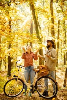Jesienna para jedzie na rowerze w parku ludzie aktywni na świeżym powietrzu jesienna kobieta brodaty m...