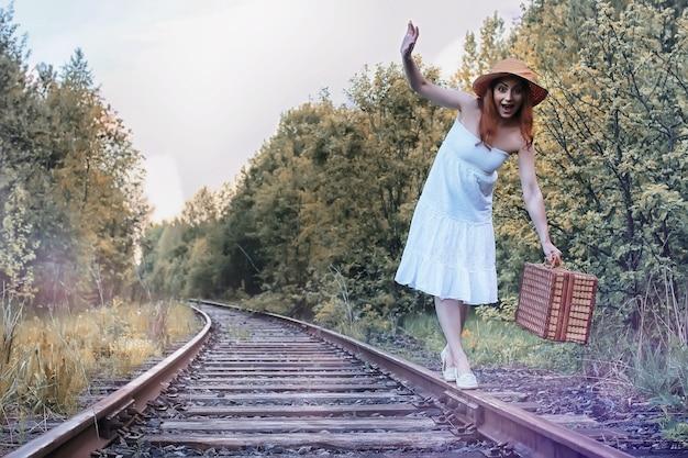 Jesienna parkowa dziewczyna w białej sukience i wiklinowej walizce chodząca po szynach