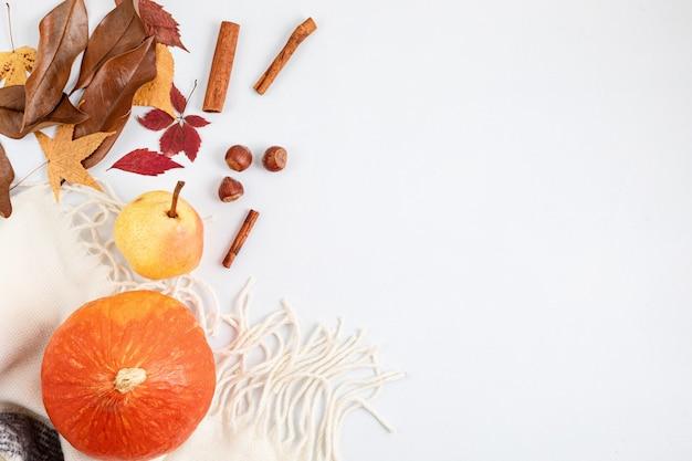 Jesienna płaska kompozycja świeża dynia, gruszka, suszone liście i orzechy na białym tle