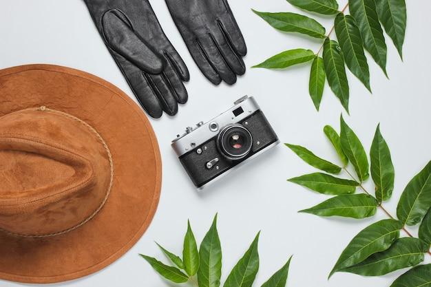 Jesienna podróż. akcesoria damskie, retro aparat na białym tle z zielonymi liśćmi. filcowy kapelusz, skórzane rękawiczki. widok z góry