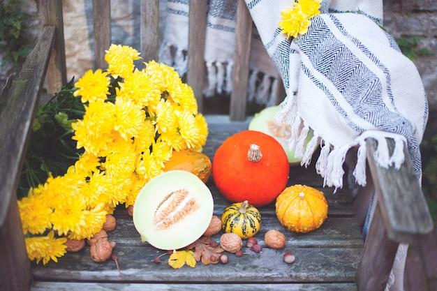 Jesienna przyroda. spadają owoce na drewno. święto dziękczynienia. jesienne warzywa na starym krześle w ogrodzie, wolne miejsce na tekst, żółte kwiaty