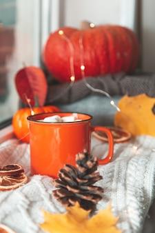 Jesienna przytulna kompozycja. kubek kakao, dynia, jesienne liście i dzianinowy koc na parapecie. jesień, domowy nastrój hygge. selektywne skupienie.
