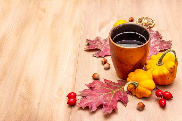 Jesienna przytulna kompozycja nastroju. gorąca herbata w szkle ceramicznym, jesienne liście, dynie, wrzosiec, orzechy laskowe