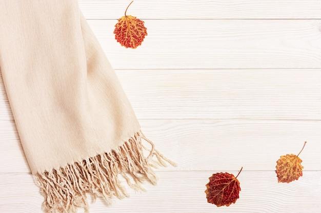 Jesienna przytulna kompozycja z suszonymi liśćmi osiki i pastelowego beżu szalika na drewnianym tle
