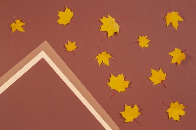 Jesienna rama kompozycji wykonana z jesiennych liści klonu na brązowym tle