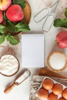 Jesienna szarlotka. składniki na szarlotkę, charlotte i pusty notatnik do napisania tekstu, przepisu.