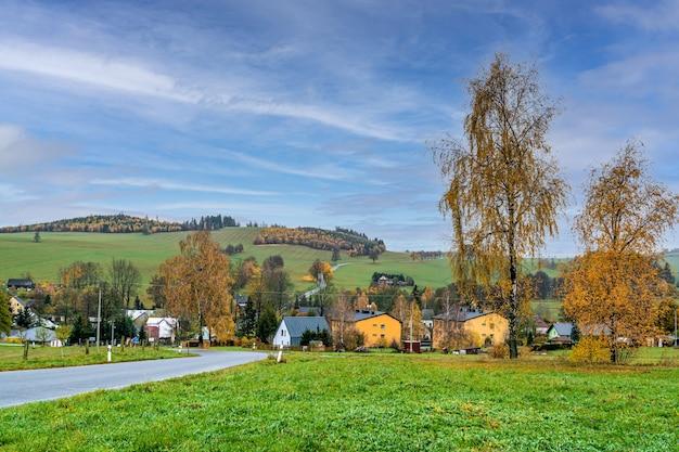 Jesienna wiejska panorama z widokiem na wieś, drzewa i pola.