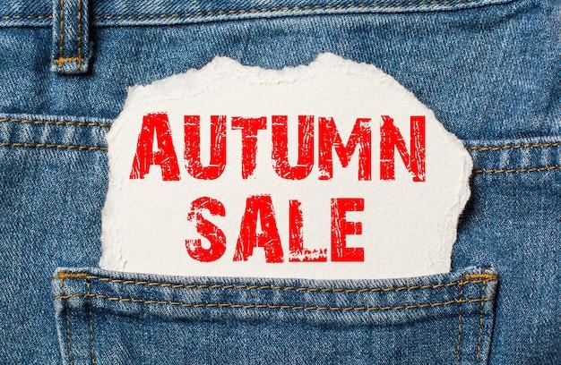 Jesienna wyprzedaż na białym papierze w kieszeni niebieskich dżinsów