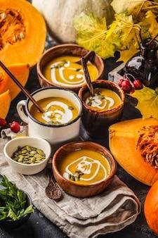 Jesienna zupa dyniowa z kremem w filiżankach, jesienne dekoracje