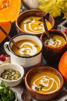 Jesienna zupa dyniowa z kremem w kubkach, jesienna sceneria. koncepcja zdrowej żywności wegańskiej.