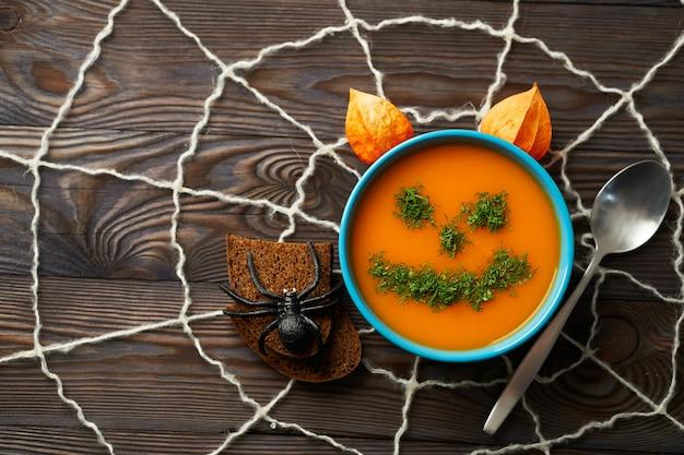 Jesienna zupa kremowa przyozdobiona koperkiem w postaci śmiesznych twarzy halloweenowe dynie.