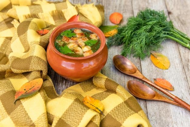 Jesienna zupa z grzankami i ziołami w glinianych garnkach.