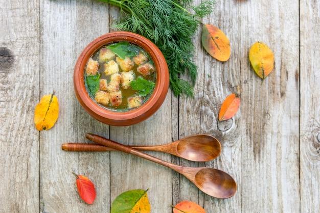 Jesienna zupa z krakersami w glinianym garnku.