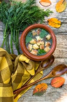 Jesienna zupa z warzyw i grzanek na drewnianym tle.