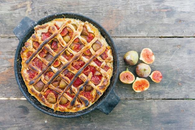Jesienne ciasto figowe lub tarta z cynamonem na starym drewnianym stole. widok z góry