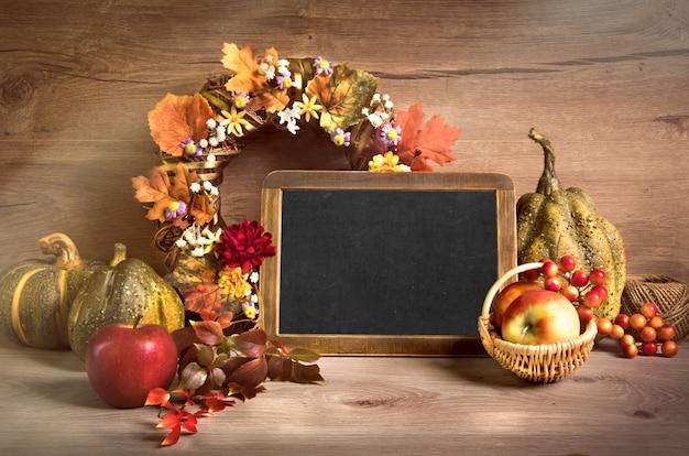 """Jesienne dekoracje i napis """"hello autumn"""" napisany na tablicy"""