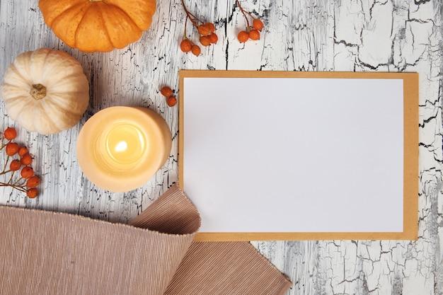 Jesienne dekoracje: serwetka z dyni i jagody na rustykalnym stole oraz biała notatka blokowa, widok z góry,