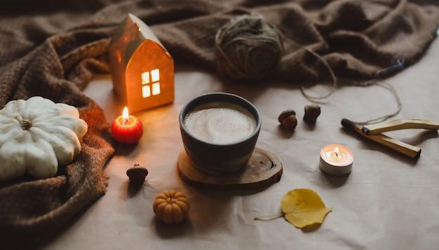 Jesienne detale martwej natury w przytulnym domowym wnętrzu z filiżanką świec w kratę hygge halloween i podzięk...