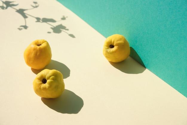 Jesienne dojrzałe żółte owoce pigwy na miętowo-zielonym papierze warstwowym