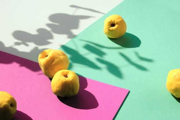 Jesienne dojrzałe żółte owoce pigwy na różowo-miętowym papierze warstwowym