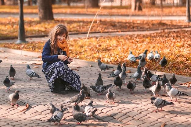 Jesienne dziecko karmi gołębie w jesiennym parku