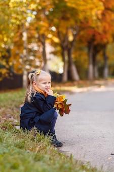 Jesienne dziecko z żółtymi liśćmi klonu w jesiennym parku