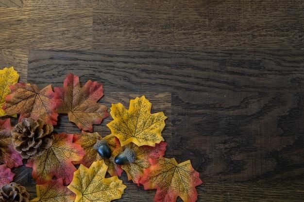 Jesienne elementy, takie jak liście, żołędzie i szyszka w lewej połowie obrazu na drewnie