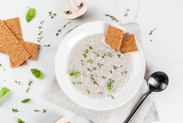 Jesienne gorące potrawy. zupy wegańskie. zupa krem z pieczarek z brązowymi smażonymi pieczarkami i ziołami, tymianek. na białym marmurowym stole. widok z góry lato
