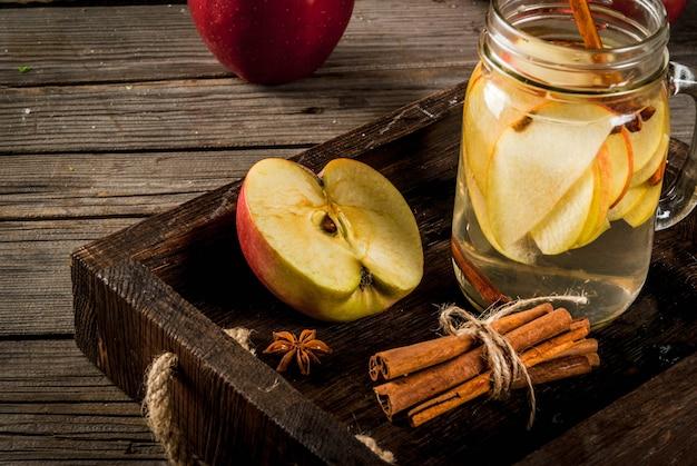 Jesienne i zimowe napoje. jesienna woda detoksykacyjna z jabłkiem, cynamonem i gruszką w słoiku z kamienia. na rustykalnym tle starego drewna, ze składnikami. skopiuj miejsce