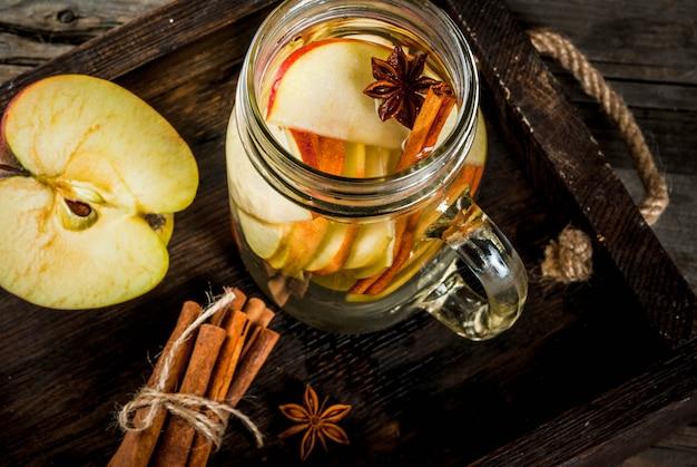 Jesienne i zimowe napoje. jesienna woda detoksykacyjna z jabłkiem, cynamonem i gruszką w słoiku z kamienia. na rustykalnym tle starego drewna, ze składnikami. zamknij widok