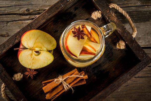 Jesienne i zimowe napoje. jesienna woda detoksykacyjna z jabłkiem, cynamonem i gruszką w słoiku z kamienia. na starym rustykalnym drewnie z dodatkami. widok z góry