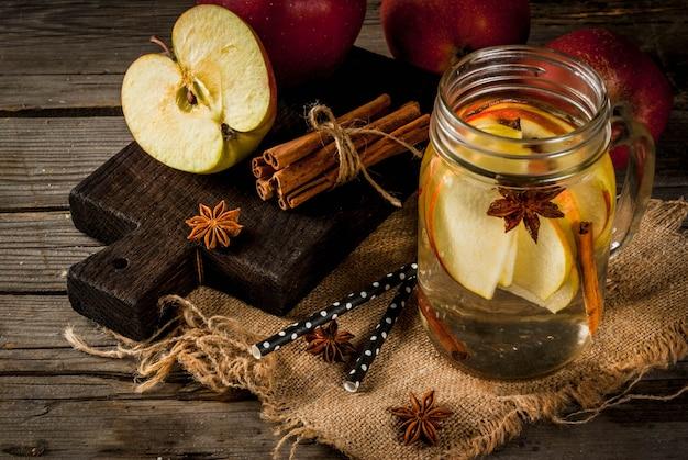 Jesienne i zimowe napoje. jesienna woda detoksykacyjna z jabłkiem, cynamonem i gruszką w słoiku z kamienia. na starym rustykalnym drewnie z dodatkami.