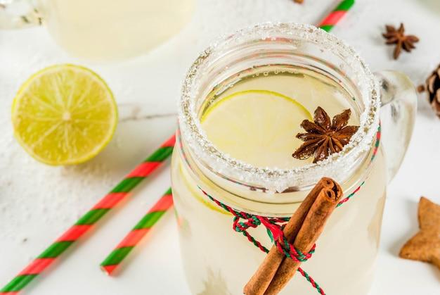 Jesienne i zimowe napoje. napój świąteczny. świąteczny koktajl śnieżkowy z sokiem z limonki, cynamonem, likierem, cukrem i gwiazdkami anyżu. na białym stole z świątecznych dekoracji, copyspace