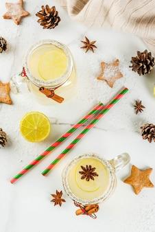 Jesienne i zimowe napoje. napój świąteczny. świąteczny koktajl śnieżkowy z sokiem z limonki, cynamonem, likierem, cukrem i gwiazdkami anyżu. na białym stole z świątecznych dekoracji, widok z góry copyspace
