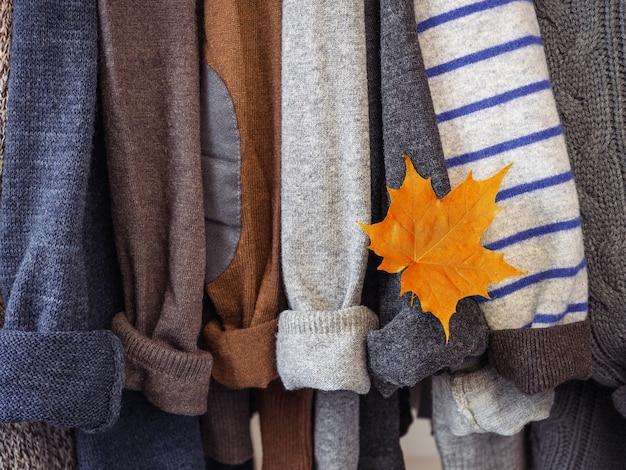Jesienne i zimowe ubrania wiszące na wieszakach w garderobie