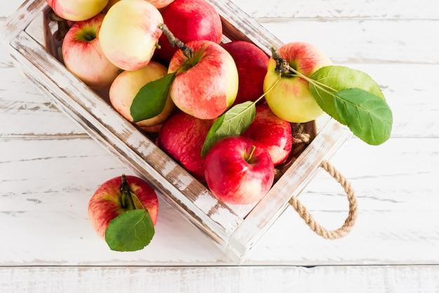 Jesienne jabłka sezonowe w białym pudełku na drewnianym tle.