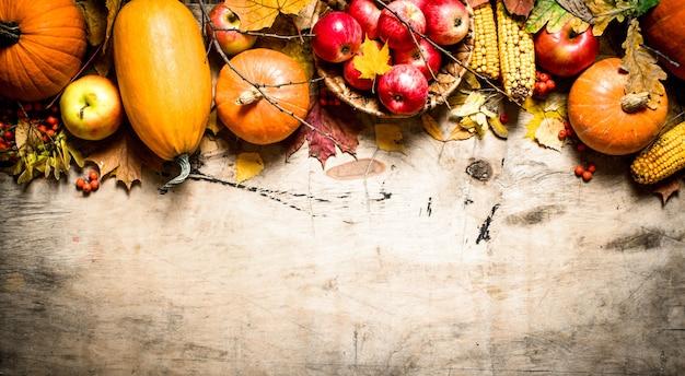 Jesienne jedzenie. jesienne owoce i warzywa. na drewnianym tle.