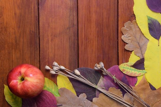 Jesienne kolorowe liście i jabłko leżą na drewnianym brązowym tle jest pusta przestrzeń