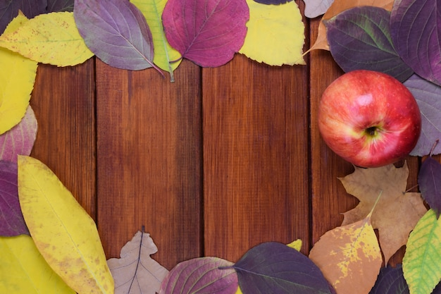 Jesienne kolorowe liście i jabłko leżą na drewnianym brązowym tle