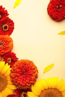 Jesienne kompozycje kwiatowe ze słoneczników, liści i kwiatów na beżowym tle, widok z góry. kreatywna kompozycja. zdjęcie pionowe