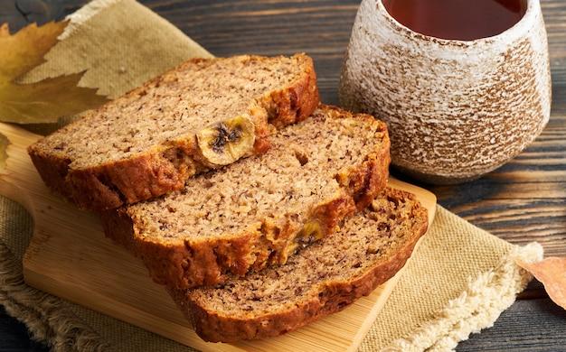 Jesienne kromki chleba bananowego, filiżanka herbaty, suche liście, ciemny drewniany stół. widok z boku.