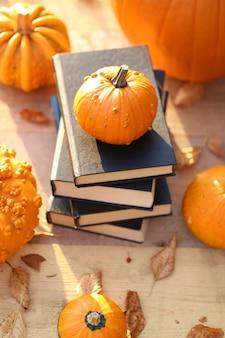 Jesienne książki. książki na halloween. stos książek z czarną okładką i zestawem pomarańczowych dyń