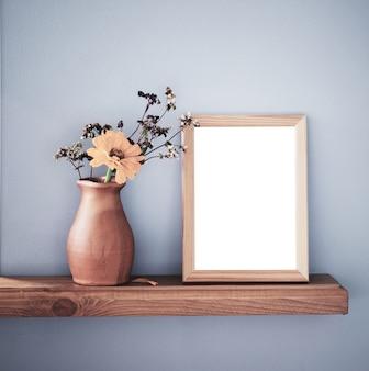 Jesienne kwiaty w rustykalnym ceramicznym wazonie i na białym tle rama na szarej ścianie w tle