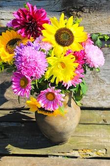 Jesienne kwiaty w rustykalnym glinianym dzbanku na drewnianym tle
