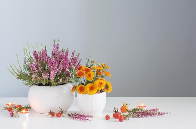 Jesienne kwiaty z płonącymi świeczkami na białym stole